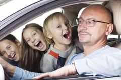 Szczęśliwy ojciec z dziećmi w samochodzie Obrazy Stock