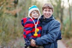 Szczęśliwy ojciec z jego synem na ręce outdoors zdjęcia stock