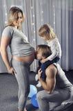 Szczęśliwy ojczulek z córką na jego brać na swoje barki całować jego wife's brzucha Obrazy Stock
