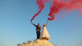 Szczęśliwy państwa młodzi falowanie barwił różowego dym przeciw niebieskiemu niebu i śmiać się honeymoon romans związek pośrodku obrazy royalty free