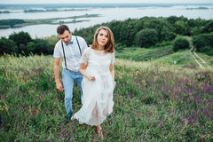 Szczęśliwy państwa młodzi odprowadzenie na zielonej trawie zdjęcia royalty free