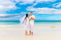 Szczęśliwy państwo młodzi ma zabawę na tropikalnej plaży zdjęcie royalty free
