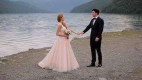 Szczęśliwy państwo młodzi na tle rzeka Piękny odbicie nowożeńcy w wodzie zbiory wideo