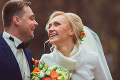 Szczęśliwy państwo młodzi przy parkiem na ich dniu ślubu zdjęcia royalty free