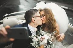 Szczęśliwy państwo młodzi robi selfie przy ich ślubem w retro samochodzie zdjęcia royalty free