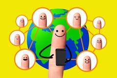 Szczęśliwy palcowy używa telefon komórkowy z światową mapą, Ogólnospołeczna sieć c fotografia stock