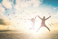 Szczęśliwy para mężczyzna, kobieta i skaczemy na pięknym tła pojęciu dla relaksujemy styl życia fotografia stock