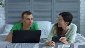 Szczęśliwy para networking z cyfrowymi przyrządami na łóżku zbiory wideo