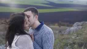 Szczęśliwy para stojak przy skałą, dotykami i buziakami w wietrznym dniu, 4K zbiory wideo