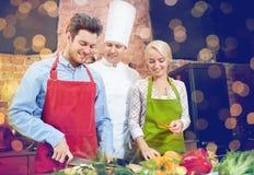Szczęśliwy pary i samiec szef kuchni gotuje kucharstwo w kuchni zdjęcia royalty free