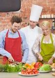 Szczęśliwy pary i samiec szef kuchni gotuje kucharstwo w kuchni Fotografia Stock