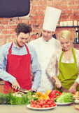Szczęśliwy pary i samiec szef kuchni gotuje kucharstwo w kuchni Zdjęcie Stock