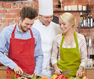 Szczęśliwy pary i samiec szef kuchni gotuje kucharstwo w kuchni Obrazy Stock