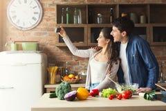 Szczęśliwy pary kucharstwo i brać selfie w kuchni Fotografia Stock