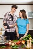 Szczęśliwy pary kucharstwo z elektroniczną książką w kuchni Obraz Royalty Free