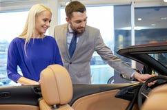 Szczęśliwy pary kupienia samochód w auto przedstawieniu lub salonie Obraz Stock