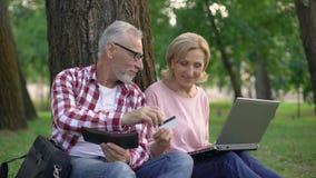 Szczęśliwy pary obsiadanie na trawie i wybierać nowych towary na laptopie, robi zakupy online zdjęcie wideo