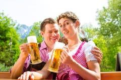 Szczęśliwa para w piwa ogrodowym pije piwie obrazy royalty free
