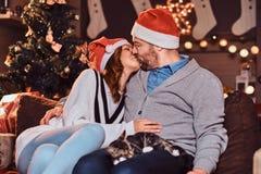 Szczęśliwy pary odświętności wigilii buziak w domu podczas gdy siedzący na kanapie Bożenarodzeniowy wakacje obrazy royalty free