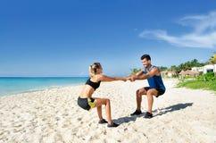 Szczęśliwy pary rozciąganie przy plażą obraz royalty free