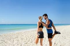 Szczęśliwy pary rozciąganie przy plażą zdjęcia stock