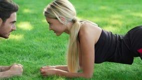 Szczęśliwy pary szkolenia deski ćwiczenie w lato parku Sport pary pojęcie zbiory wideo