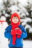 Szczęśliwy pięknego dziecka budynku bałwan w ogródzie, zima czas Obrazy Stock