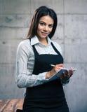 Szczęśliwy piękny żeński kelner w fartuchu fotografia stock