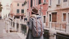 Szczęśliwy piękny żeński turystyczny cieszy się chodzi patrzeć wokoło wzdłuż wodnej kanałowej ulicy w Wenecja Włochy zwolnionym t zbiory