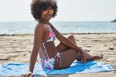 Szczęśliwy piękny afro amerykański kobiety obsiadanie na ręczniku na plaży Fotografia Stock