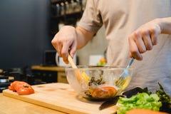 Szczęśliwy piękny azjatykci mężczyzna przygotowywa sałatkowego jedzenie w kuchni Młody azjatykci męski kulinarny zdrowy jedzenie  Obraz Stock