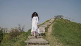 Szczęśliwy piękny kobiety chodzenie zestrzela schodki na zielonym wzgórzu i pozować dla kamery zdjęcie wideo