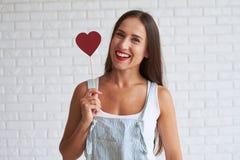 Szczęśliwy piękny kobiety mienia czerwieni papier kierowy jej twarz blisko obrazy stock