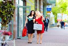 Szczęśliwy plus wielkościowy kobiet robić zakupy zdjęcia stock