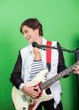 Szczęśliwy podpisany Bawić się gitarę Podczas gdy Śpiewający Wewnątrz Obrazy Stock
