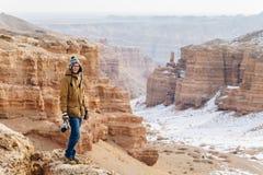 Szczęśliwy podróżnik z kamery stojakami na krawędzi falezy w Charyn jarze w Kazachstan zdjęcia royalty free