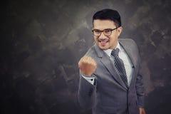 Szczęśliwy pomyślny gestykuluje biznesmen, odizolowywający nad cegła plecy zdjęcia stock