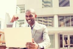Szczęśliwy pomyślny młody człowiek z laptopem świętuje sukces obraz royalty free