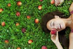 Szczęśliwy portret piękna dziewczyna na trawie otaczającej brzoskwiniami Zdjęcia Stock