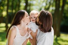 szczęśliwy portret rodzinny Młody ciemnowłosy ojciec i jego piękna żona całujemy ich uroczej dziecko córki obrazy stock