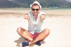 Szczęśliwy posadzony młody człowiek wskazuje jego dotyka Fotografia Stock