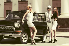 Szczęśliwy potomstwo mody mężczyzna i kobiety obok rocznika samochodu Obraz Stock