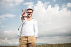 Szczęśliwy potomstwo mody mężczyzna pokazuje zwycięstwo znaka zdjęcia royalty free