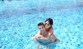 Szczęśliwy potomstwo pary przytulenie w basenie Zdjęcia Stock