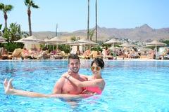 Szczęśliwy potomstwo pary przytulenie w basenie Fotografia Stock