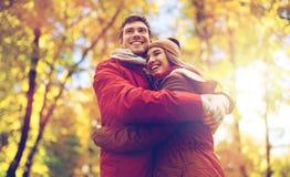 Szczęśliwy potomstwo pary przytulenie w jesień parku zdjęcie royalty free