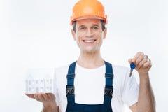 Szczęśliwy pozytywny inżynier trzyma klucz obrazy stock