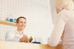 Szczęśliwy pozytywny mężczyzna robi płatności gotówkowej non Obrazy Stock