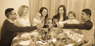 Szczęśliwy pozytywny multigenerational rodzinny obsiadanie przy wakacje stołem Zdjęcia Royalty Free