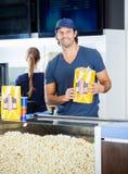 Szczęśliwy pracownika mienia popkornu Paperbag Przy Fotografia Royalty Free